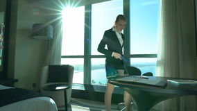 性感的年轻白肤金发的女商人在电话谈话在旅馆客房或办公室,结束成交 商业对人立场手提箱行程负无法认出 影视素材