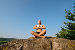 性感的年轻运动妇女画象有强健的身体实践的瑜伽的在岩石 背景蓝天 库存照片