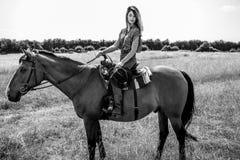 性感,美丽,有蓝眼睛骑乘马的女牛仔与在草的领域的西部马鞍在大农场的 免版税库存照片