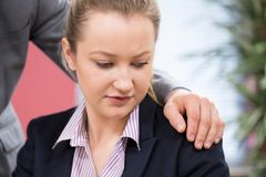 性扰乱女性同事的商人在办公室 免版税库存图片