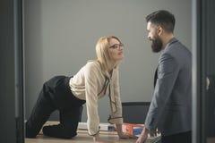 性调情的人在工作 性感的秘书在办公室诱惑上司 桌面看看的女实业家有胡子的商人 人 免版税库存图片