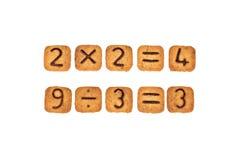 总和由与巧克力数字的方形的曲奇饼制成在他们 背景查出的白色 免版税库存图片