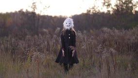 总图 在秋天领域,在熊面具的女孩跳舞 妇女在蓝色外套4K缓慢的Mo打扮 股票视频