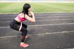 总是在良好状态 跳跃体育的衣物的现代年轻女人,当行使户外时 与地方的健身背景为 免版税库存照片