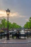 恋人一起坐在俯视一条运河的微明在阿姆斯特丹 免版税库存照片