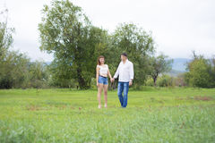 恋人供以人员和走在绿色领域的妇女 免版税库存照片
