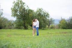 恋人供以人员和走在绿色领域的妇女 免版税库存图片