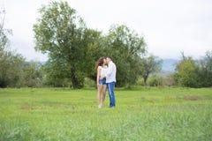 恋人供以人员和走在绿色领域的妇女 库存照片