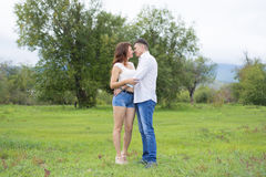 恋人供以人员和走在绿色领域的妇女 库存图片