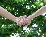 恋人在庭院里结合握手 免版税库存照片