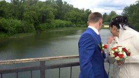 恋人在永远将丢失的河锁在篱芭的锁并且投掷钥匙 在桥梁的衣物柜象征 影视素材