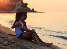 年轻恋人在沙子坐岸 免版税库存图片
