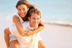 恋人在获得的爱结合在海滩画象的乐趣 免版税库存图片