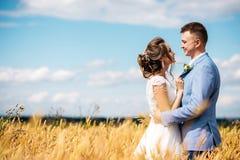 恋人在麦田中间的新娘和新郎容忍 免版税库存图片