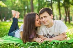 年轻恋人在说谎在草的公园 免版税库存图片