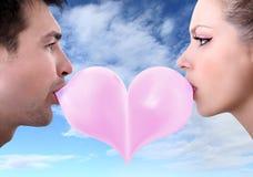 恋人夫妇亲吻与口香糖的心形的情人节 免版税库存照片