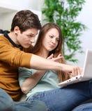 恋人夫妇使用有担心的态度的一台计算机 免版税库存图片