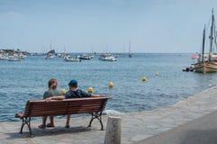 恋人夫妇坐长凳在海岸附近 免版税库存照片