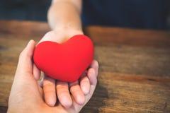 恋人夫妇` s递结合在一起使一个红色心脏标志 免版税库存照片