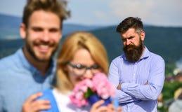 恋人拥抱室外调情的人浪漫史联系 在爱约会的夫妇,当嫉妒的有胡子的欺诈他时的人观看的妻子 免版税库存照片