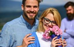 恋人拥抱室外调情的人浪漫史联系 在爱约会的夫妇,当嫉妒的有胡子的欺诈他时的人观看的妻子 免版税图库摄影
