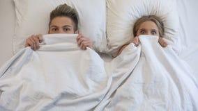 恋人捉住在床上由父母,困窘和害怕,看起来冲击 库存图片