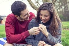 恋人男孩给一朵雏菊她的女朋友 免版税库存图片