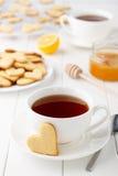 恋人的浪漫早餐在情人节:两杯茶和心形的曲奇饼在白色木桌上 图库摄影