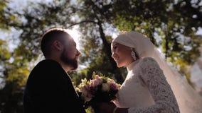 恋人看彼此与在美丽的太阳的光芒的微笑 照相机移动小 股票录像