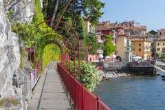 恋人红色庭院曲拱步行带领往美丽和古城瓦伦纳的海岸线的在科莫湖边缘 免版税库存照片