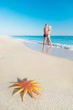 恋人结合在与大红色海星的含沙海海滩 库存图片