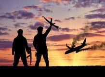 恐怖分子剪影和炸毁飞机 库存照片