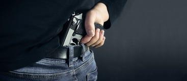 恐怖分子窃贼人在他的手上的拿着枪 隐藏的枪 查出在黑暗的背景 复制空间 免版税库存图片