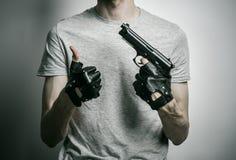 恐怖和火器题目:与一杆枪的凶手在他的在黑手套的手上在灰色背景在演播室 库存照片