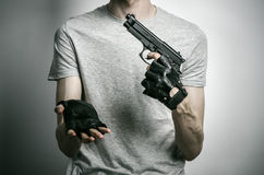 恐怖和火器题目:与一杆枪的凶手在他的在黑手套的手上在灰色背景在演播室 库存图片