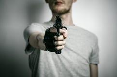 恐怖和火器题目:与一杆枪的凶手在他的在黑手套的手上在灰色背景在演播室 免版税库存照片