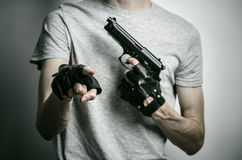 恐怖和火器题目:与一杆枪的凶手在他的在黑手套的手上在灰色背景在演播室 免版税库存图片