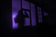 恐怖概念 一个人的剪影有被喷洒的胳膊的在窗口前面 做的照片2012年8月9日 库存照片