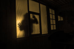 恐怖概念 一个人的剪影有被喷洒的胳膊的在窗口前面 做的照片2012年8月9日 免版税库存图片