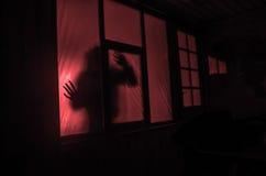 恐怖概念 一个人的剪影有被喷洒的胳膊的在窗口前面 做的照片2012年8月9日 库存图片