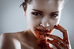 恐怖美丽的吸血鬼妇女特写镜头纵向有血液的 免版税库存照片