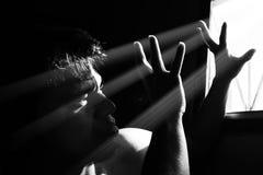 恐惧单独人与光的黑暗的从窗口 库存图片