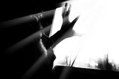 恐惧单独人与光的黑暗的从窗口 免版税库存照片