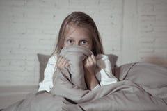 恐惧的失眠的逗人喜爱的女孩在掩藏在毯子后的晚上害怕黑暗和妖怪 库存照片
