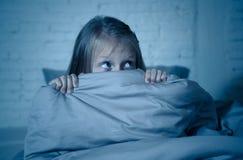 恐惧的失眠的逗人喜爱的女孩在掩藏在毯子后的晚上害怕黑暗和妖怪 图库摄影