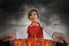 恐慌的年轻无经验的家庭厨师妇女与拿着罐的围裙烧在与在恐慌的火焰 库存图片