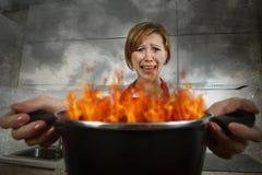 恐慌的年轻无经验的家庭厨师妇女与拿着罐的围裙烧在与在恐慌的火焰 图库摄影