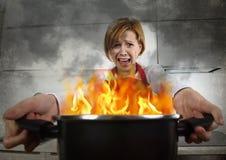 恐慌的年轻无经验的家庭厨师妇女与拿着罐的围裙烧在与在恐慌的火焰 免版税图库摄影
