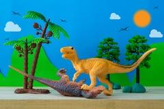 恐龙在狂放的模型背景的战斗场面 库存照片