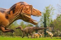 恐龙陈列在植物的公园 免版税库存照片